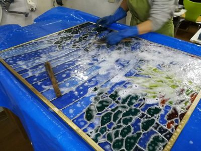 組立ての終わったパネルをプールで洗浄しています