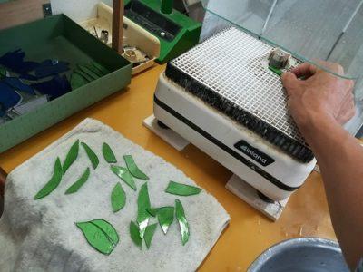 緑のガラスをルーターを使って研磨中