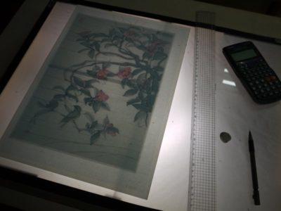 ライトボックス上で、水墨画の原画を方眼紙にトレースしています